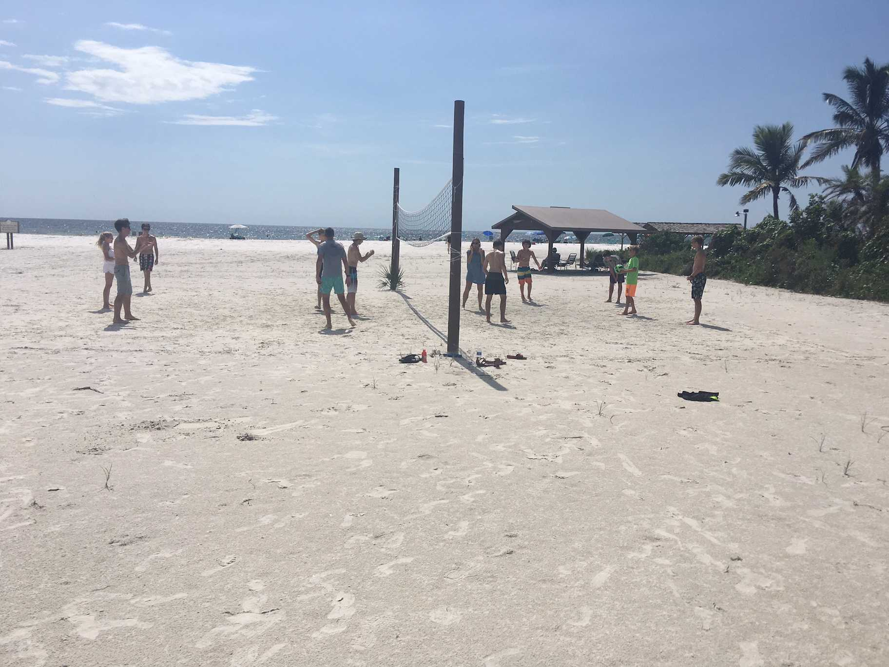 The runners and coaches of the ODA Cross Country team play a heated game of volleyball on the beach.