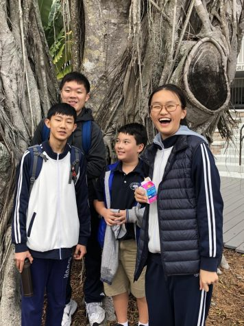 Chinese Exchange visitors pose near the banyan on the Lower Campus with ambassador, Bobby.
